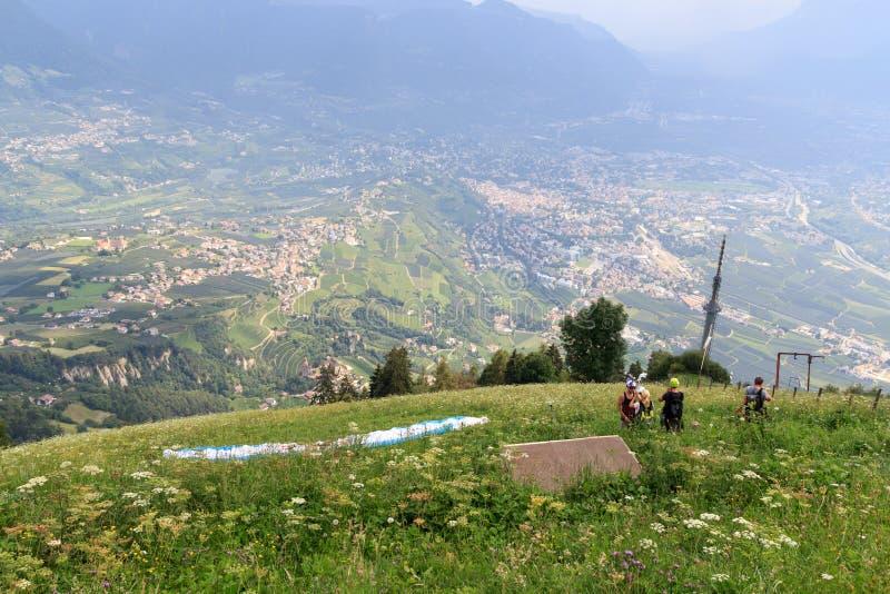 Les parapentistes se préparent au parapentisme devant le panaroma de Merano au Tyrol du sud photos stock