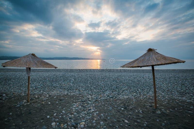Les parapluies avec un toit de canne se tiennent sur la plage à côté de la mer à l'aube photo stock
