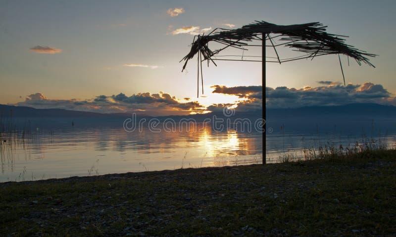 Les parapluies de Reed dans le coucher du soleil échouent au lac d'Ohrid photographie stock