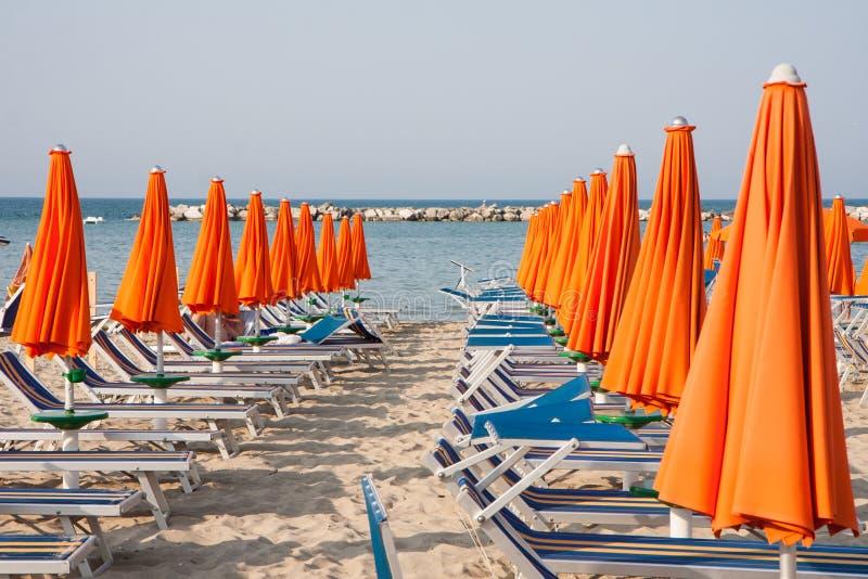 Les parapluies et les lits pliants à Rimini et Riccione et Cattolica échouent image stock