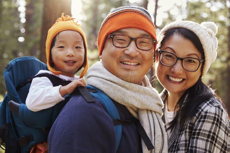 Les parents asiatiques portant la fille d'enfant en bas âge dans la forêt, se ferment  photographie stock