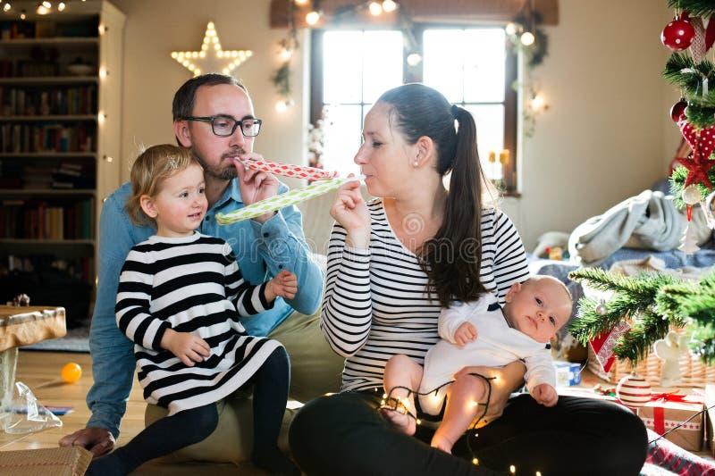 Les parents avec des enfants à la partie de soufflement d'arbre de Noël siffle image stock