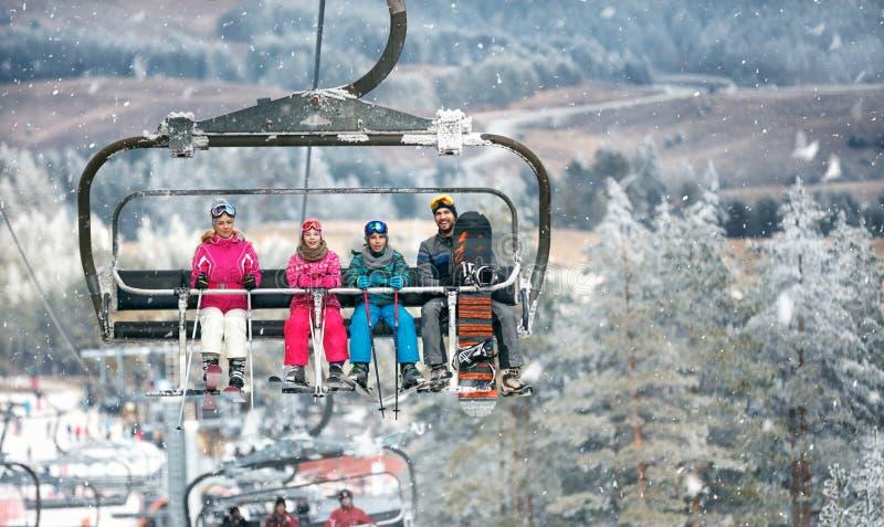 Les parents avec des enfants dans le remonte-pente s'élève sur le terrain de ski photographie stock libre de droits