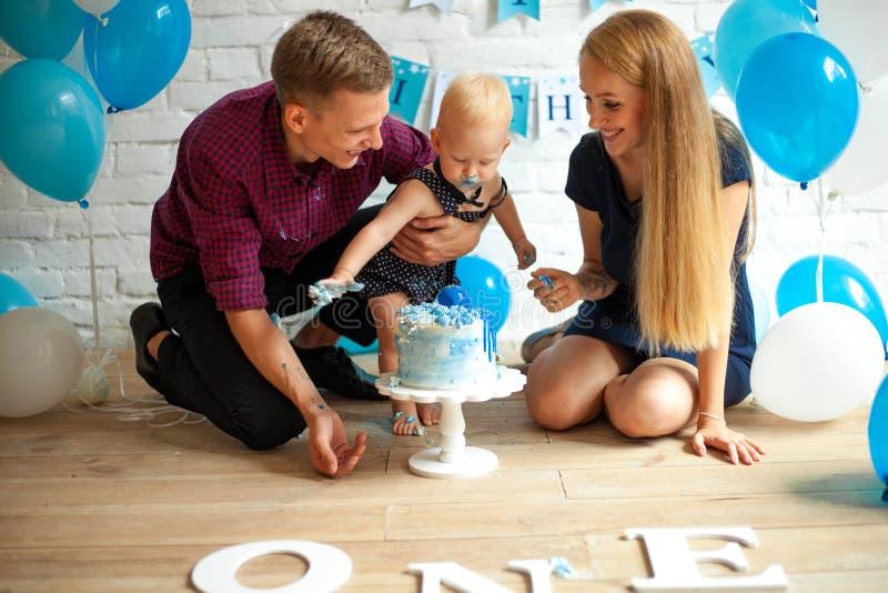 Les parents célèbrent le premier anniversaire de leur fils et alimentent le sien par le gâteau photo stock