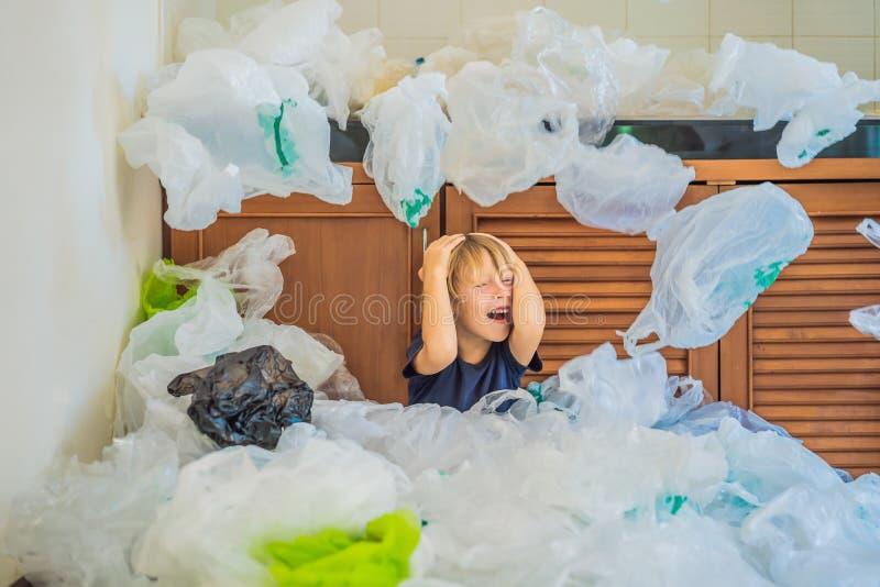 Les parents du gar?on ont employ? trop de sachets en plastique qu'ils ont rempli la cuisine enti?re Concept de rebut z?ro Le conc photo stock