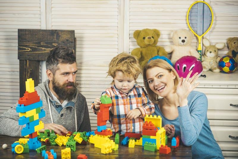 Les parents et l'enfant avec les visages heureux font des constructions en briques photographie stock libre de droits