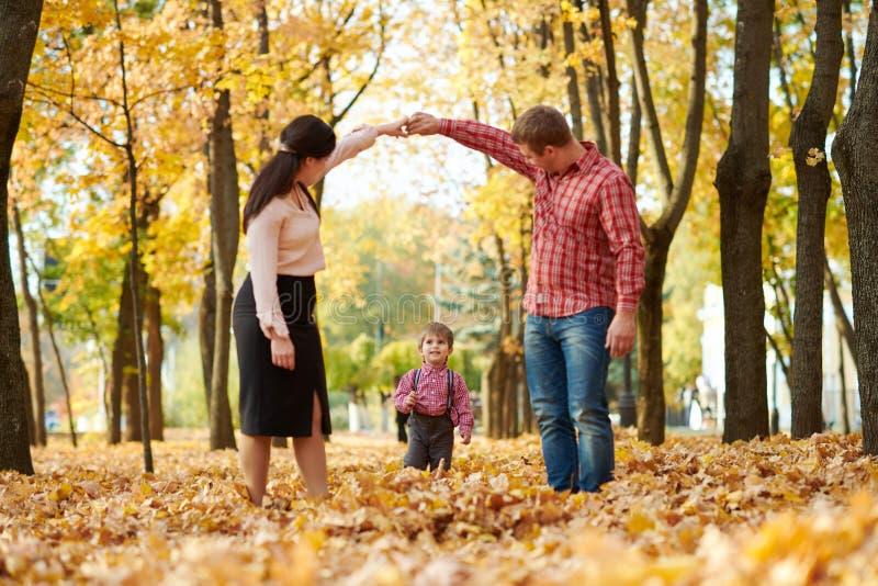 Les parents et l'enfant marchent en parc de ville d'automne Arbres jaunes lumineux photos stock