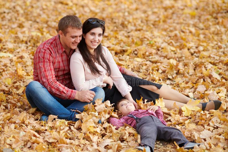 Les parents et l'enfant s'asseyent en parc de ville d'automne Arbres jaunes lumineux image libre de droits