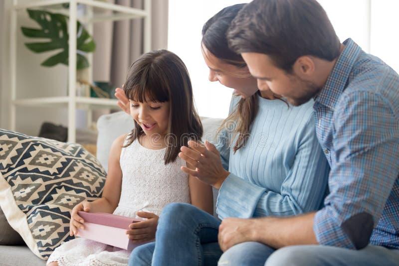 Les parents f?licitent la fille mignonne faisant le cadeau d'anniversaire image libre de droits