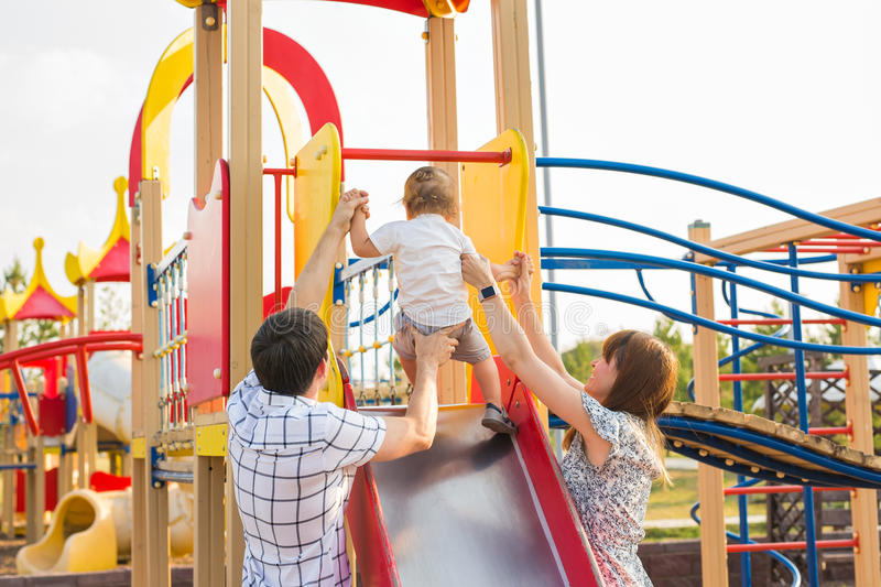 Les parents heureux avec le fils jouant au ` s d'enfants glissent images libres de droits