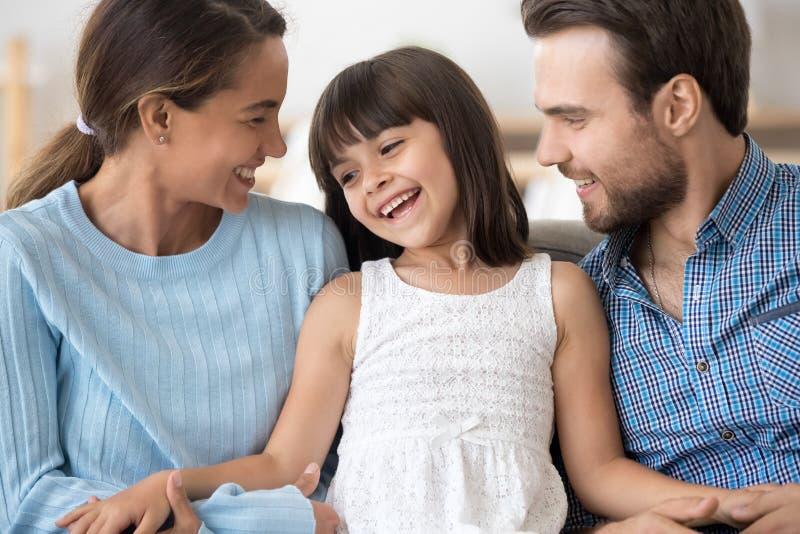 Les parents heureux d?tendent sur le divan avec peu de fille photo libre de droits