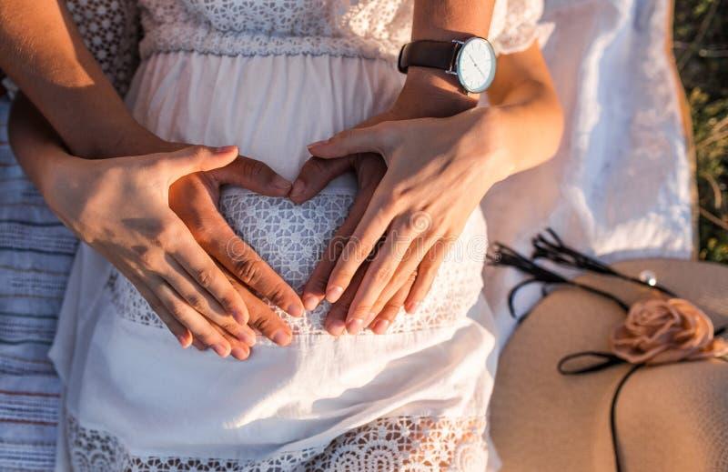Les parents heureux tiennent le ventre enceinte image stock