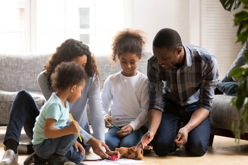 Les parents noirs et les petits enfants jouent l'image ensemble de peinture images libres de droits