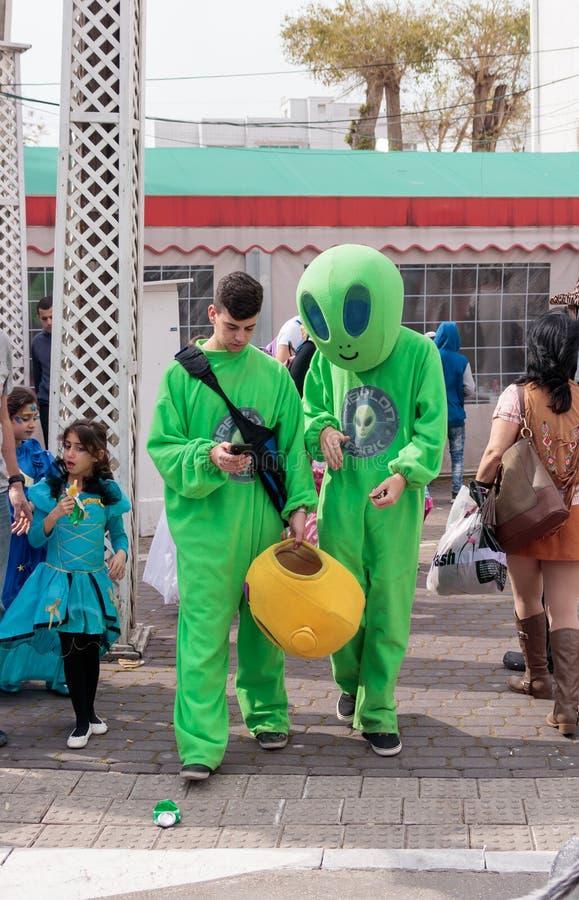 Les participants au carnaval dans des costumes d'étrangers marchent le long de s images libres de droits