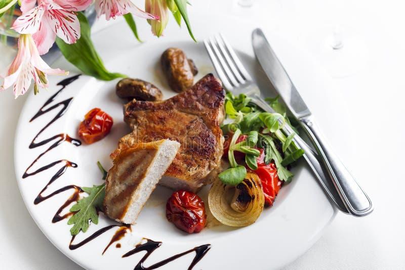 Les parties juteuses épaisses succulentes de filet grillé ont servi avec des tomates et des légumes de rôti images libres de droits