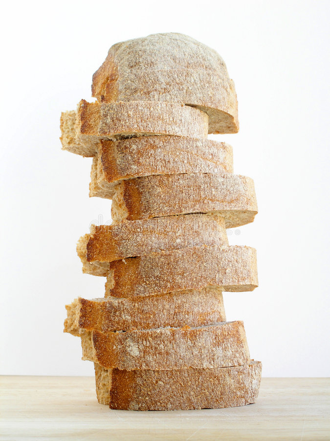 Les parts du pain pilled vers le haut sur le panneau de découpage images stock