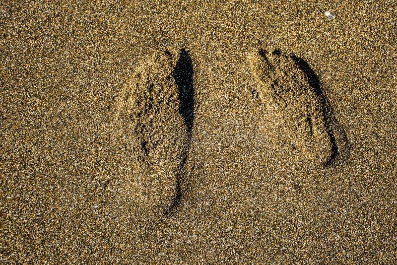 Les pas couplent dans le sable images libres de droits