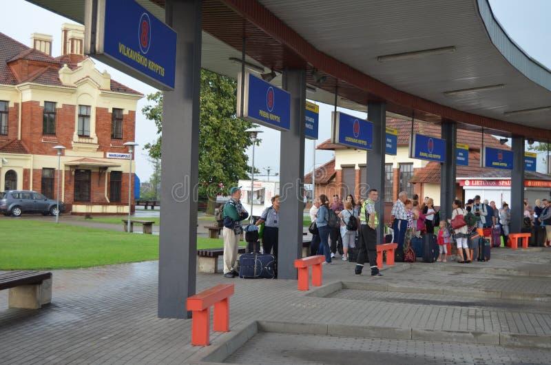 Les passagers attendent l'arrivée de l'autobus à une station dans Mariampol, Lettonie photographie stock libre de droits