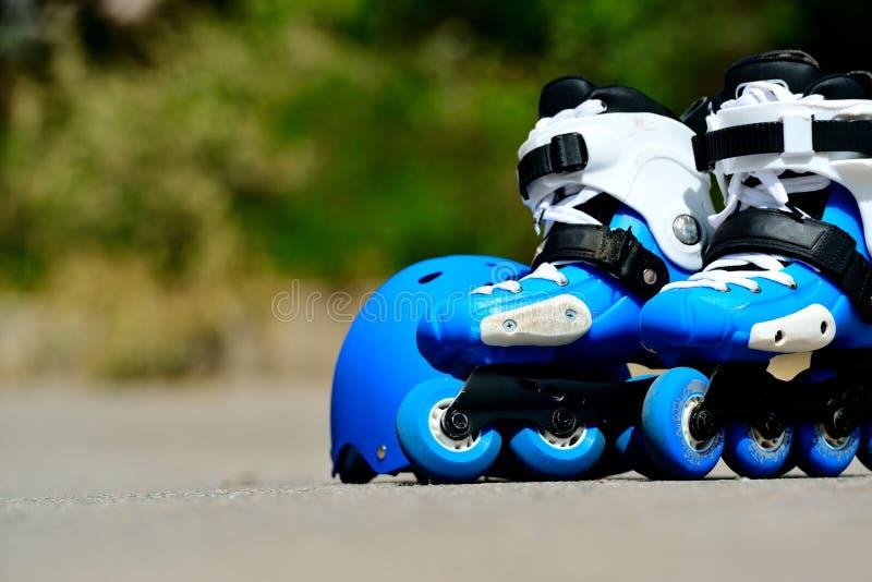 Les patins intégrés de rouleau avec le casque dans le patin se garent sur le fond gris d'asphalte images libres de droits