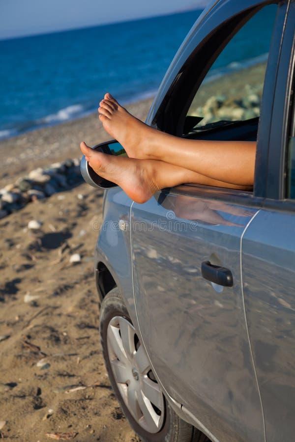 Les pattes de la femme balançant à l'extérieur un hublot de véhicule images stock