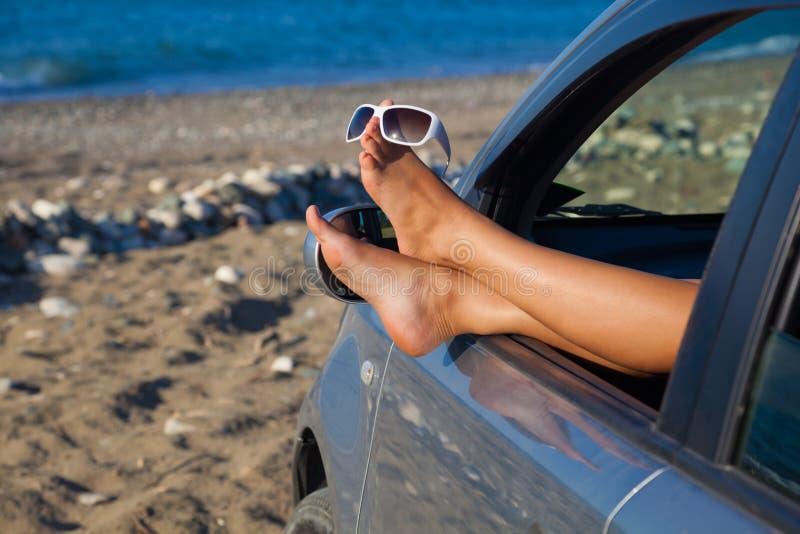 Les pattes de la femme balançant à l'extérieur un hublot de véhicule photos libres de droits