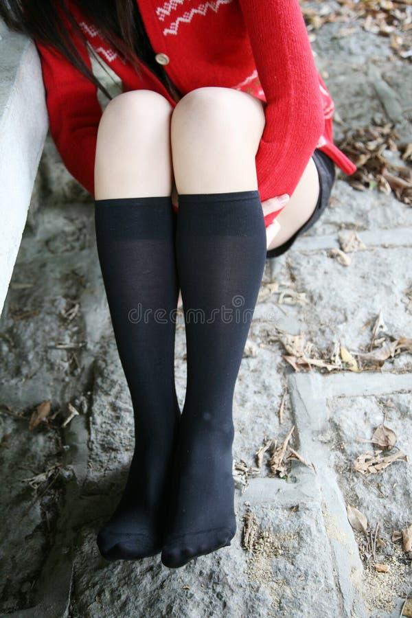 Les pattes de la fille portant de longues chaussettes image stock