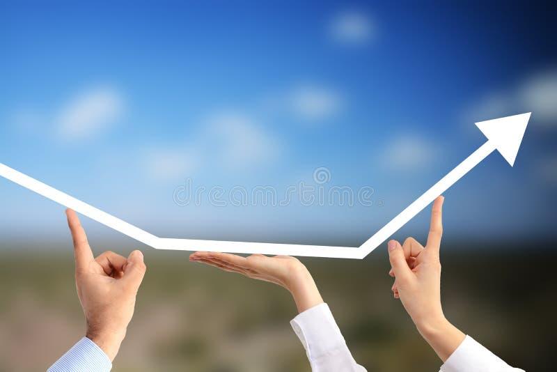 Les people's d'affaires remet tenir une flèche allante haute suggérant les avantages du travail d'équipe sur un fond agricole d photographie stock libre de droits