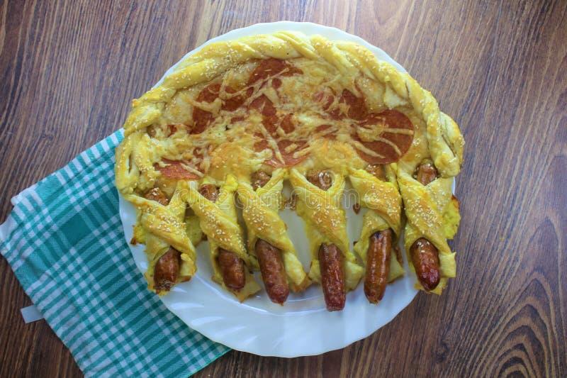 Les pepperoni fantastiques de pizza de nourriture roulent et les petits pains de saucisse avec du fromage et les graines de sésam images libres de droits