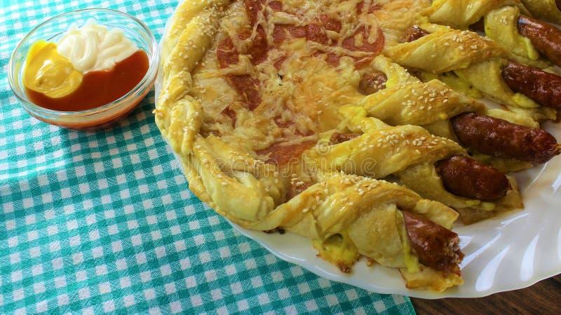 Les pepperoni fantastiques de pizza de nourriture roulent et les petits pains de saucisse avec du fromage et les graines de sésam photos libres de droits