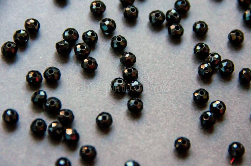Les perles colorées et noires et les pierres ont isolé le fond gris photographie stock
