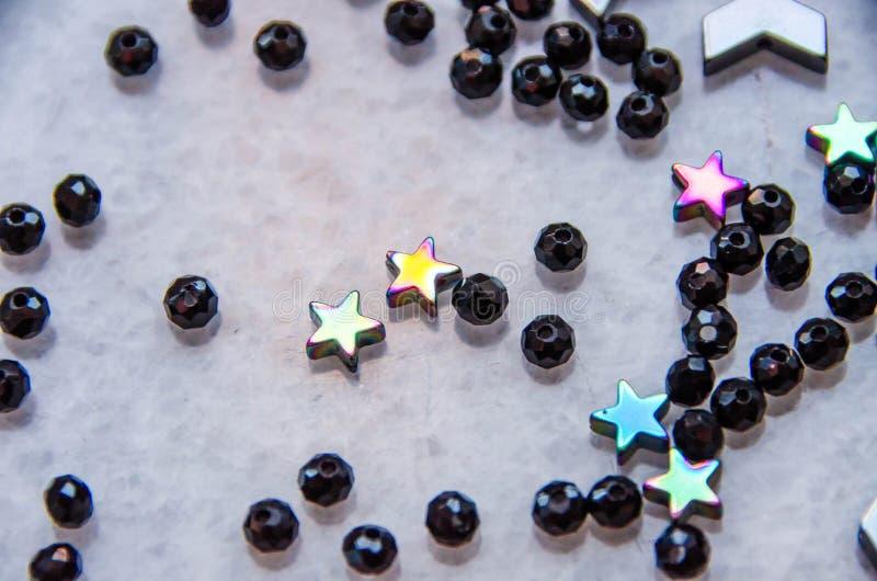 Les perles colorées et noires et les pierres ont isolé le fond gris image stock