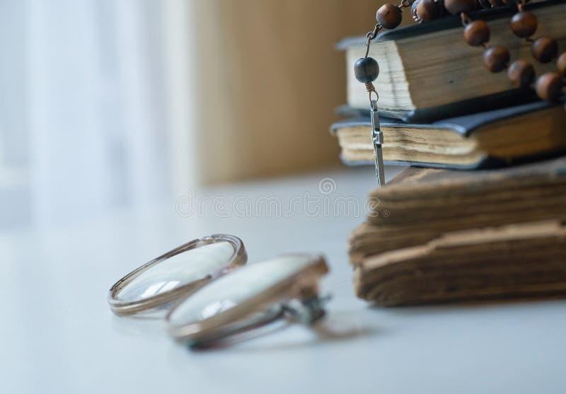 Les perles de chapelet sur des livres de liturgie d'église catholique et de vieux verres du côté de eux photos stock