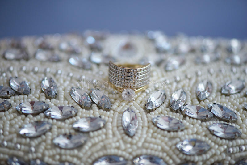 Les perles et la fausse pierre d'isolement ont embelli l'embrayage avec ses alliances, sur un tissu bleu de cuir de suède photographie stock