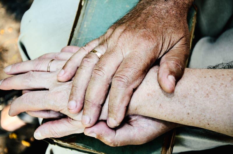 Les personnes âgées équipe la main tient la main de la femme agée image teintée de couleur photos libres de droits