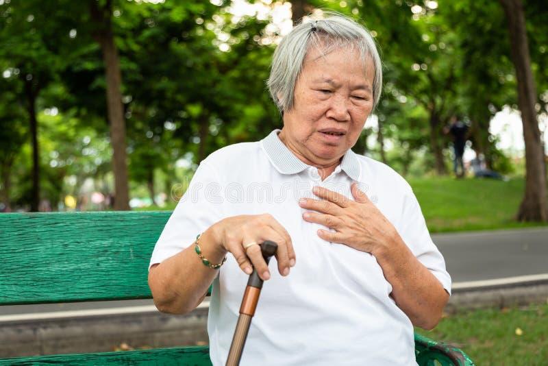 Les personnes âgées asiatiques avec certains symptômes, difficulté respirant, douleur ou problèmes de coeur, communiquent les sym image stock