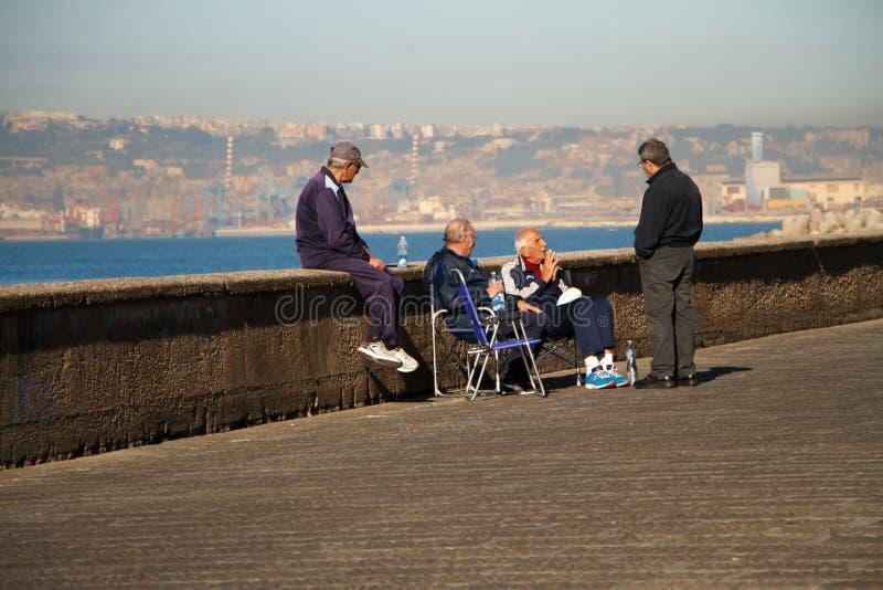 Les personnes âgées s'asseyant sur la promenade de Naples sont détendantes et parlantes parmi elles-mêmes dans la perspective du  photos libres de droits