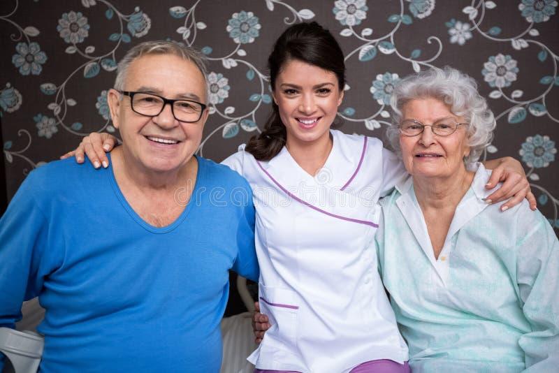 Les personnes âgées satisfaisantes de sourire avec l'infirmière photographie stock libre de droits