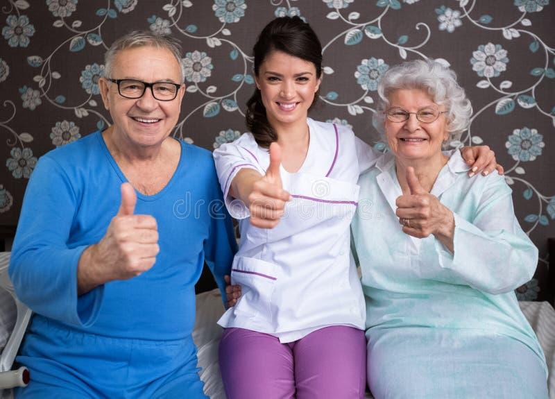 Les personnes âgées satisfaisantes de sourire avec l'infirmière photo stock