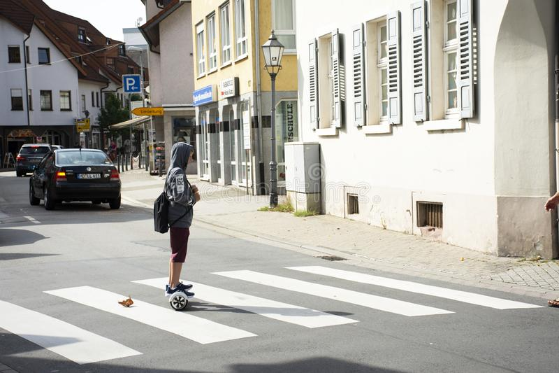 Les personnes allemandes de garçon jouent et les roues d'équilibre de monte traversant la route à Heidelberg, Allemagne photo stock