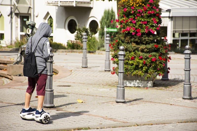 Les personnes allemandes de garçon jouent et les roues d'équilibre de monte traversant la route à Heidelberg, Allemagne photographie stock libre de droits