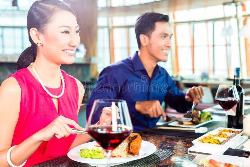 Les personnes asiatiques affinent diner dans le restaurant photographie stock libre de droits