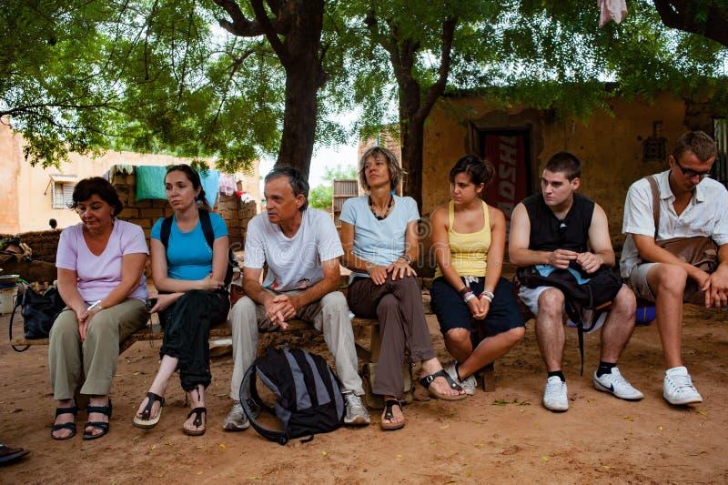 Les personnes caucasiennes blanches et les personnes d'africain noir apprécient la vie dans un village rural images stock