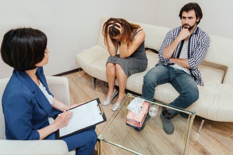 Les personnes désespérées s'asseyent dans la chambre avec le thérapeute et travaillent avec elle La fille regarde vers le bas et  images stock