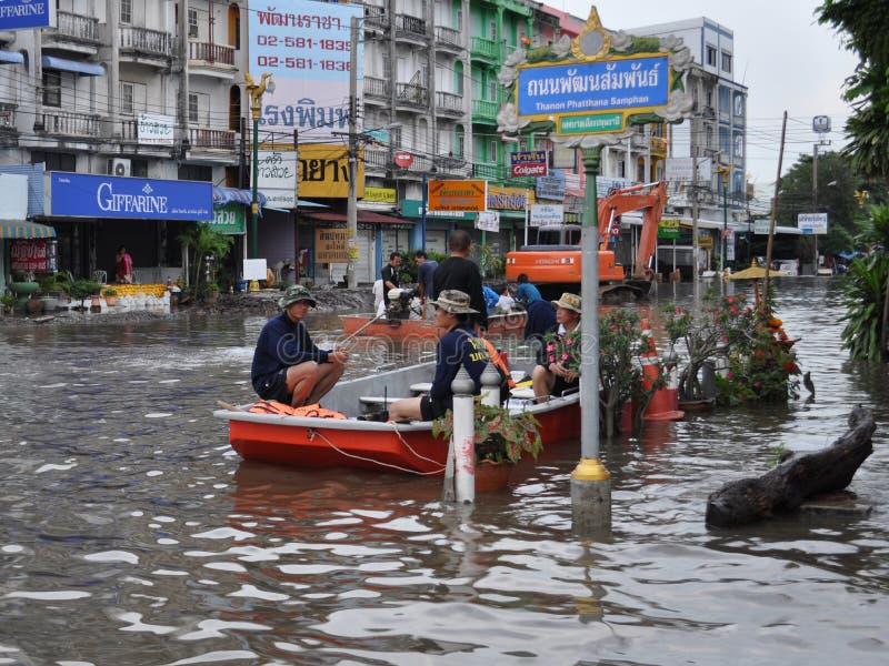 Les personnes de délivrance attendent dans leur bateau dans une rue inondée de Pathum Thani, Thaïlande, en octobre 2011 photographie stock