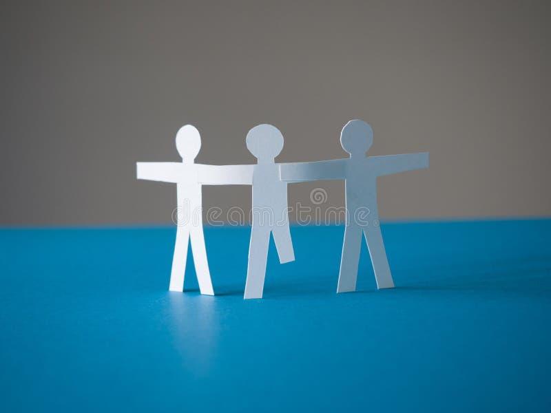 Les personnes de papier se tiennent ensemble L'un d'entre eux est handicapé image libre de droits