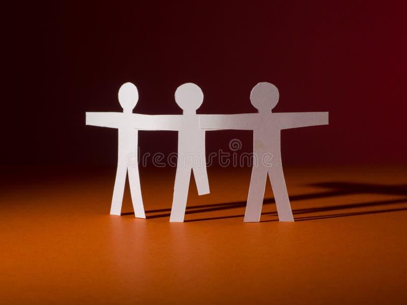 Les personnes de papier se tiennent ensemble L'un d'entre eux sans jambes photo libre de droits
