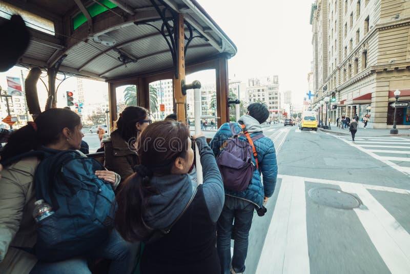 Les personnes de touristes apprécient le tour sur le tram ouvert célèbre à San Francisco photo libre de droits