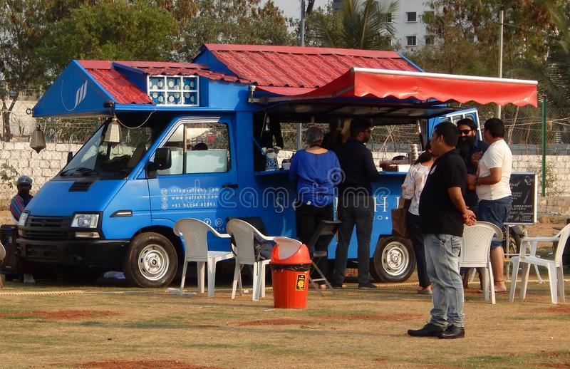 Les personnes indiennes achètent la nourriture de rue aux camions de nourriture postés dans le terrain découvert photo stock