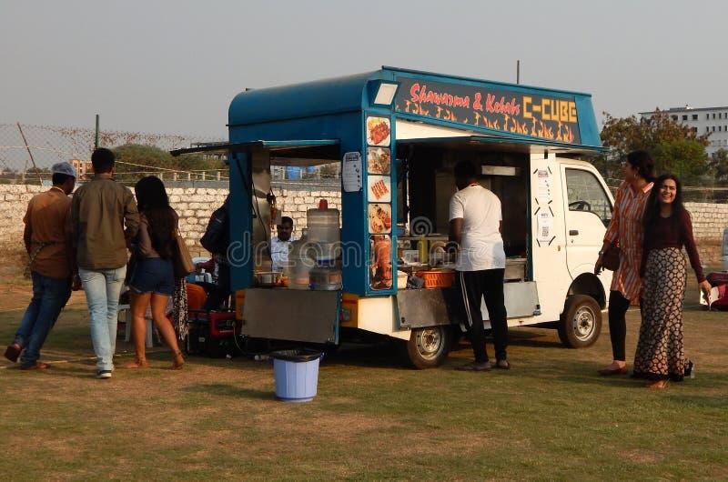 Les personnes indiennes achètent la nourriture de rue aux camions de nourriture postés dans le terrain découvert photographie stock libre de droits