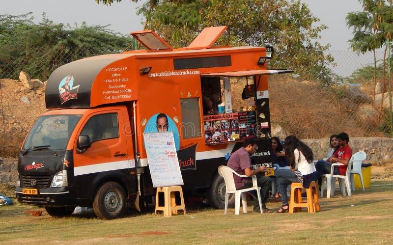 Les personnes indiennes achètent la nourriture de rue aux camions de nourriture postés dans le terrain découvert photos stock